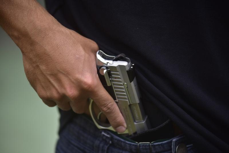 Eduardo Aguiar, instrutor de tiro, empunha arma